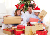 Young family having fun with Christmas gifts — Stock Photo