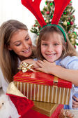 Smiling mother and her daughter holding Christmas gifts — Stock Photo