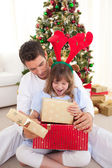 Happy father and his daughter opening Christmas gifts — Stockfoto