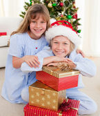 Smiling siblings holding Christmas gifts — Stock Photo