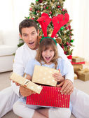 Surprised father and his girl opening Christmas gifts — Stock Photo