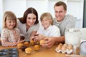 Famiglia sorridente mangiare loro muffin in cucina — Foto Stock