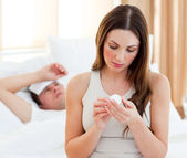Attentive woman giving medicine to her sick husband — Stock Photo