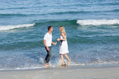 Enamoured couple walking at the seaside — Stock Photo