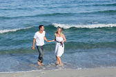 Romantic couple walking at the seaside — Stock Photo