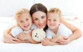 Hermanos animados con su madre en una cama — Foto de Stock