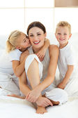 Cute children kissing their mother sitting on a bed — Stock Photo