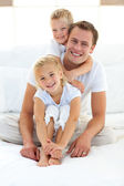 Cute blond boy hugging his dad sitting on a bed — Stockfoto