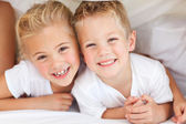 Adorable siblings playing on a bed — Stock Photo