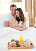 Enamoured couple having breakfast lying in bed — Stock Photo