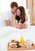 Intimate couple having breakfast lying in bed — Stock Photo