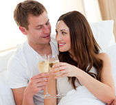 Romantic couple drinking champagne lying in bed — Stock Photo