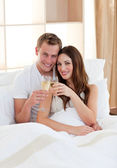 Affectionate couple drinking champagne lying in bed — Stock Photo