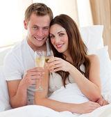 ベッドで横になっているカップル飲むシャンパンを愛する — ストック写真
