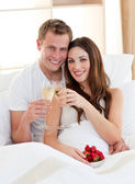 Enamoured couple drinking champagne with strawberries lying in b — Stock Photo
