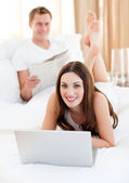 Smiling couple having activites lying on bed — Stockfoto