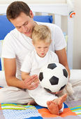 Blond little boy and his father playing with a soccer ball — Stock Photo
