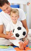 Niño sonriente y su padre jugando con una pelota de fútbol — Foto de Stock
