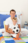 Portrait of a little boy and his father playing with a soccer ba — Stock Photo