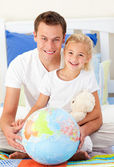 Attentive father and his daugther looking at a terrestrial globe — Stock Photo