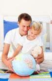 Earing father and his daugther looking at a terrestrial globe — 图库照片