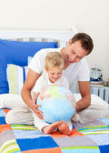 Enthousiaste vader en zijn zoon kijken naar een terrestrische globe — Stockfoto