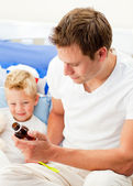 Attractive father giving cough syrup to his sick son — Stock Photo