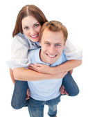 Loving couple enjoying piggyback ride — Stock Photo