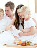 Elated family having breakfast sitting on bed — Stock Photo