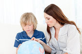Captivated child looking at a terrestrial globe with his mother — Stock Photo