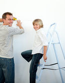 Smiling father and his son decorating a room — Стоковое фото