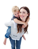Smiling mother giving her son piggyback ride — Stock Photo