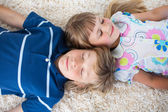 Cute siblings lying on the floor — Stock Photo