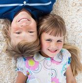 Adorable siblings lying on the floor — Stock Photo