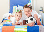 Cute little boy and his father watching a football match — Stock Photo