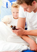 Concerned man looking after his sick son — Stock Photo