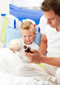 Caring man looking after his sick son — Stock Photo