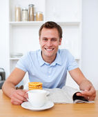 Handsome man reading newspaper during the breakfast — Stock Photo