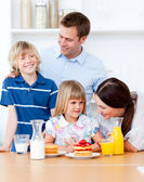 Jolly family eating breakfast in the kitchen — Stock Photo