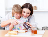 Adorable little girl and her mother preparing toasts — Stock Photo