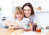 Blond little girl and her mother preparing toasts — Stock Photo