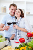 Smiling couple drinking wine while cooking — Stock Photo