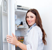 Happy woman looking for something in the fridge — Stock Photo