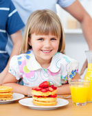 Portrait of a smiiling little girl eating waffles with strawberr — Stock Photo