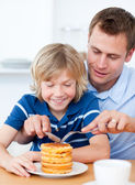 Attentive father and his son eating waffles — Stockfoto