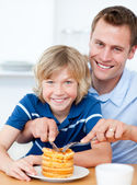 Smiling father and his son eating waffles — Стоковое фото