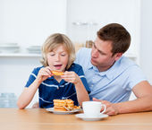 Charming father and his son eating waffles — Stock fotografie