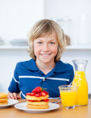 Smiling boy eating waffles with strawberries — Stock fotografie