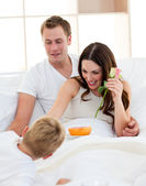 Adorable little boy having fun with his parents in the bedroom — Stock Photo