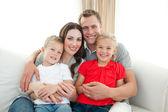 Portrait of Happy family sitting on sofa — Stock Photo